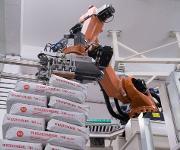 Der Roboter nimmt einzelne Säcke auf und setzt sie nach den vorgegebenen Lagenbildern auf die Ladungsträger.