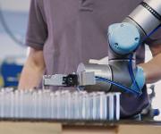 Der kollaborierende Roboter führt einer Umformungsmaschine hochsensible Glasröhrchen zu.  (Bilder: Hofmann)
