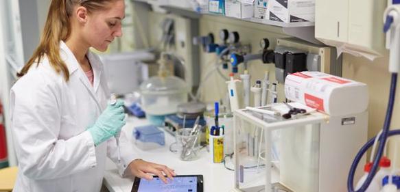 Labormitarbeiterin nutzt Tablet bei der Laborarbeit