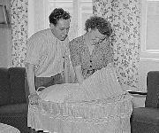 Mann und Frau an der Kinderwiege