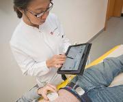 Dr. Rizky Widyaningsih aus dem Team der AVTC demonstriert, wie sich in Zukunft mittels Tablet auch Mikroimplantate steuern lassen sollen, die die Beweglichkeit des Darms im richtigen Takt halten. (Quelle: Markus Schmidt / Universitätsmedizin Mainz)