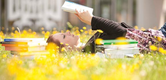 Junge Frau mit Buch in der Sonne
