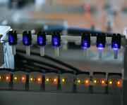 Acht Subminiatur-Lichttaster prüfen eine Achterreihe von Kunststofftuben auf Vollständigkeit
