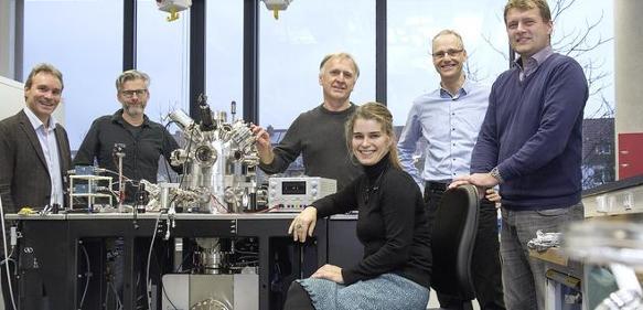 Konsortiumsmitglieder stehen um neues Elektronenmikroskop herum
