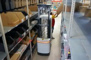 Dank Sicherheitslasern kann der Kommissionier-Roboter TORU Cube parallel zu seinen menschlichen Kollegen im selben Lagergang arbeiten. Damit kann er Mitarbeiter bei wenig ergonomischen Aufgaben, wie z.B. dem Picken aus den oberen Fächern, unterstützen. (Foto: Magazino, Test von TORU Cube bei DHL, April 2016)