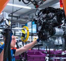 Mitarbeiter führt Industrieroboter im BMW Group Werk Regensburg