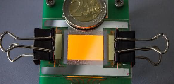 Orange leuchtende OLED auf einer Graphen-Elektrode. Die Zwei-Euro-Münze dient als Größenvergleich. (© Foto Fraunhofer FEP)
