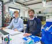 Die Doktoranden Harald Knorke (links) und Matias Fagiani am Steuerungspult des sogenannten Photodissoziationsspektrometers, mit dem die bahnbrechenden Messungen zum Gotthuß-Mechanismus durchgeführt wurden. (Foto: Universität Leipzig / Swen Reichhold)