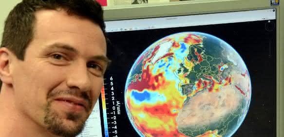 Dr.-Ing. Roelof Rietbroek vom Institut für Geodäsie und Geoinformation der Universität Bonn mit einer globalen Darstellung des Meeresspiegelanstiegs am Computer-Bildschirm. Die verschiedenen Farben bedeuten unterschiedliche Niveaus. (© Foto: Johannes Seiler / Uni Bonn)
