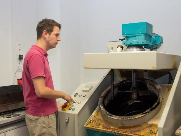 Bernhard Hofko mit der Prüfmaschine, mit der die Verarbeitbarkeit von Asphaltmischgut bei der Produktion bestimmt wird. (Bild: TU Wien)