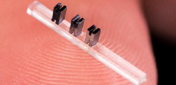 Drei Miniatur-Beschleunigermodule aus Silizium auf einem durchsichtigen Träger. (Bild: SLAC National Accelerator Laboratory)
