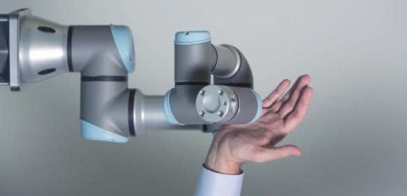 Roboterarm von Universal Robots mit menschlicher Hand