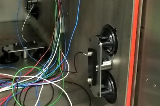 Teil des Messaufbaus für eine Schallemissionsprüfung: Wand einer Sterilisierkammer mit Kabeldurchführungen und Schallemissionssensoren in Vakuumhaltern.