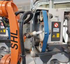 Der Roboter führt die Werkstücke zur Bearbeitung an die Doppelfreiband- und Kontaktrollen-Schleifmaschine