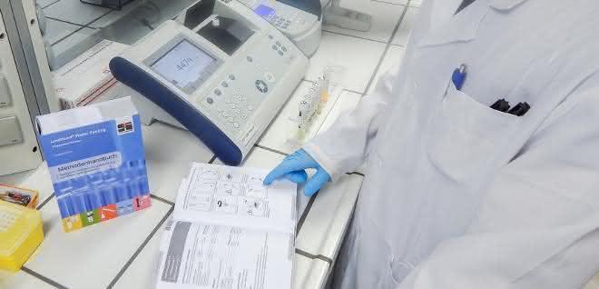 Laborant mit Nachschlagewerk