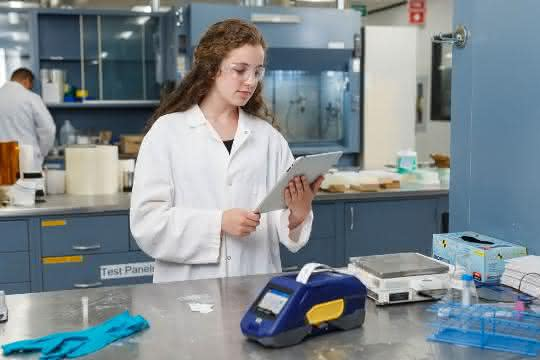 Labormitarbeiterin mit Smartphone und BradyPrinter M611