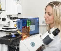 Frau im Labor an Mikroskop und Bildschirm
