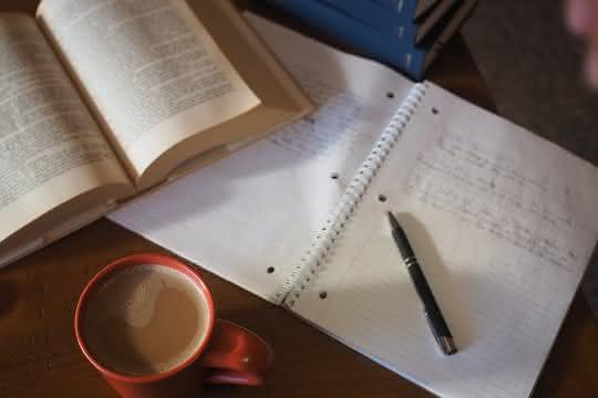 Schreibtisch mit Buch und Heft