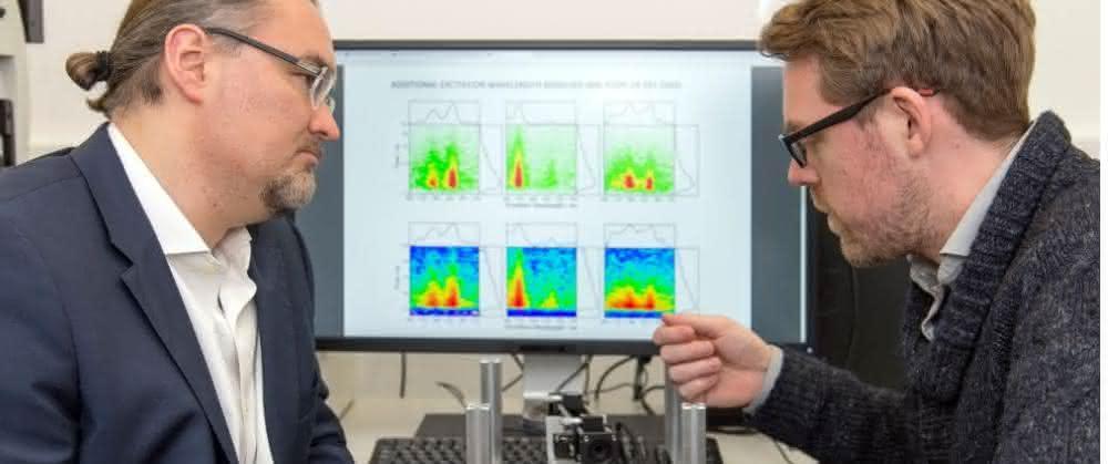 Prof. Dr. Juergen Hauer (li) und Erstautor Erling Thyrhaug mit ihrem Messinstrument. Im Hintergrund Spektren, die damit aufgenommen wurden.