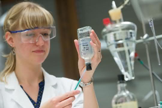 Eine biologisch-technische Assistentin, entnimmt der anaeroben Bakterienkultur eine Probe.