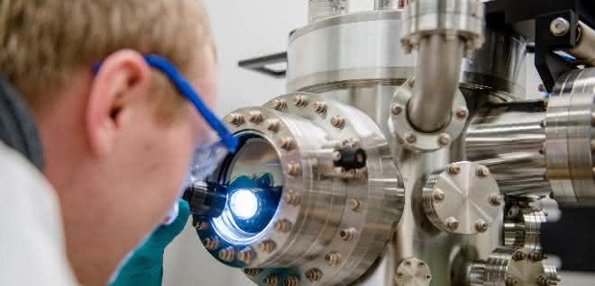 Michael Meischein vor dem Sputter-System, in dem die Nanopartikel durch simultane Beschichtung aus mehreren Quellen in einer ionischen Flüssigkeit erzeugt werden.