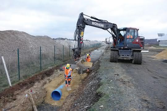 Der Rohrgraben wird mit auf die Baustelle geliefertem Ersatzmaterial verfüllt