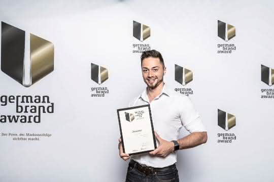Dominic Fischer, Eventmarketing Manager bei Dematic, nahm in Berlin den German Brand Award für Dematic entgegen.
