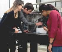 Corina Andronescu, Tsvetan Tarnev und Harshitha Barike Ayappa besprechen ein Experiment am elektrochemischen Rasterzellmikroskop.