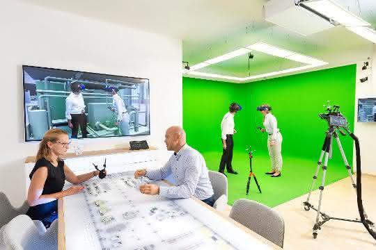 """Virtuelle Realität im """"Autodesk VR Lab"""" München: 2 Personen stehend mit VR-Brillen, auf einem Bildschirm an der Wand ein virtuelles Bild, und 2 Personen sitzen am Schreibtisch."""