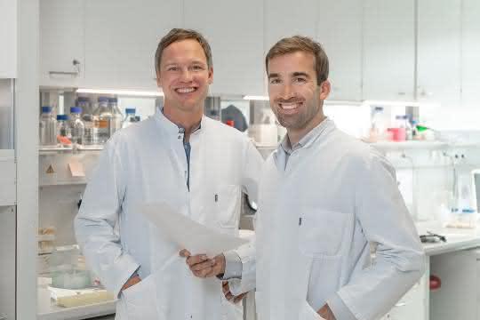 PD Dr. Hendrik Poeck und PD Dr. Simon Heidegger stehen in einem Labor, beide in weißen Kitteln.