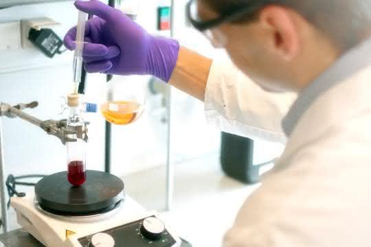 Im Labor: Mann im Kittel gibt mit Hilfe einer Spritze eine farblose Flüssigkeit in einen Glaskolben, der eine rote Flüssigkeit enthält.