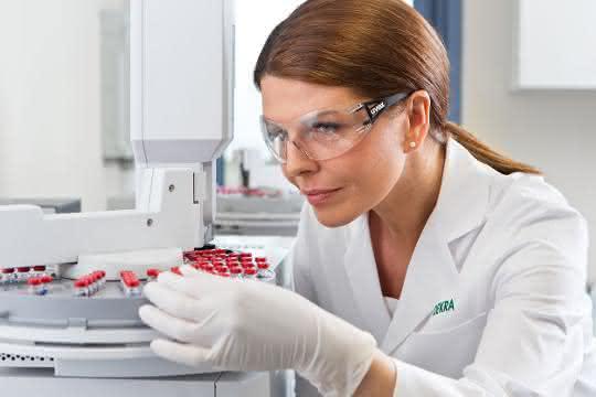 Labormitarbeiterin mit Probenröhrchen im Labor