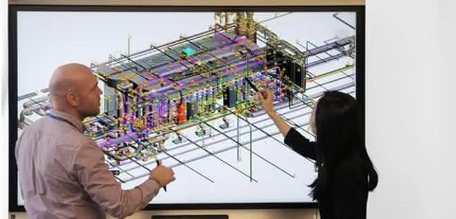 Vor einem Bildschirm mit digitalem Modell stehen eine Frau und ein Mann, die sich besprechen.