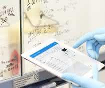 Labormitarbeitender mit Tablet vor den Scheiben eines Abzugs