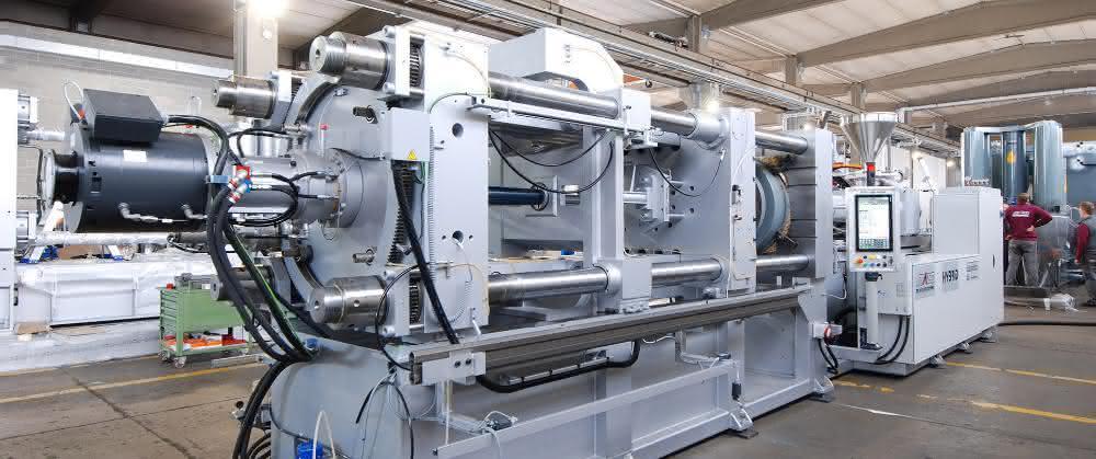 6000 Kilonewton Hybrid-Spritzgießmaschine – robuster Maschinenbau trifft modulare Automatisierung von Siemens. Links im Vordergrund der Torquemotor Simotics T-1FW3, der schnelle, präzise Schließ- und Öffnungsbewegungen des Kniehebels realisiert.