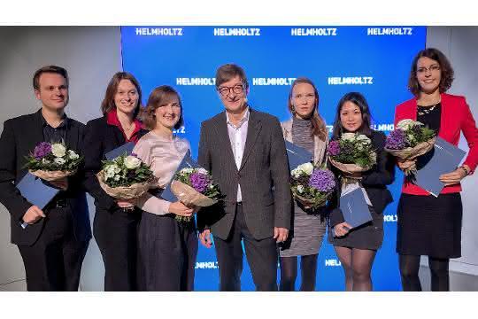 Foto von der Preisverleihung: Links und rechts vom Helmholtz-Präsidenten stehen jeweils drei Preisträger. Jeder Preisträger hält einen Blumenstrauß und eine blaue Mappe in den Händen.