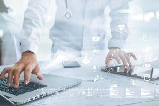 Eine Person im weißen Kittel arbeitet an einem Laptop  mit der rechten Hand und gleichzeitig mit der linken Hand an einem Tablet.