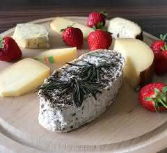 Verschiedene Käsesorten und Erdbeeren auf einem Holzbrett