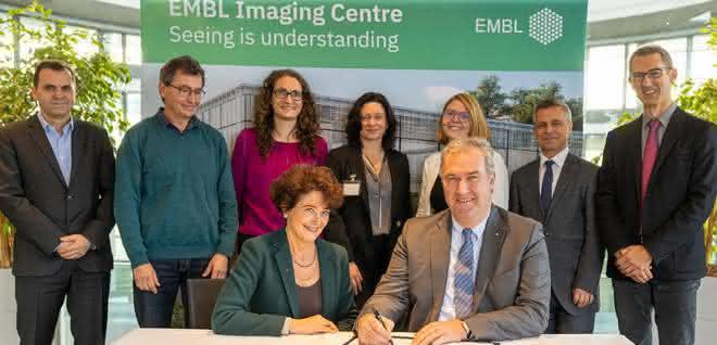 Gruppenfoto von Vertretern von Leica Microsystems und vom EMBL; im Vordergrund am Tisch sitzend Edith Hard und Markus Lusser bei der Unterzeichnung der Vereinbarung