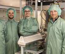 Vier Wissenschaftler in grünen Kitteln und mit grünen Haarnetzen