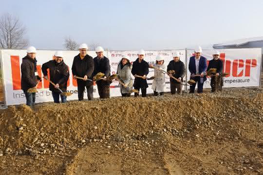 10 Personen mit weißen Bauhelmen stehen nebeneinander an einer Baugrube und heben jeder einen Spaten mit Sand.