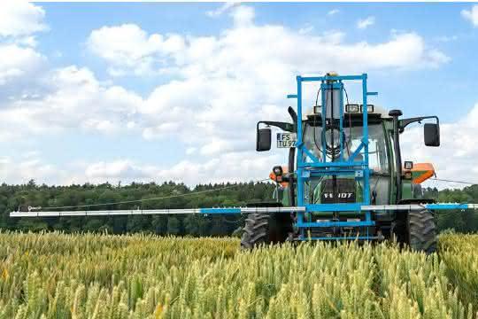 Traktor mit Düngevorrichtung auf einem Getreidefeld