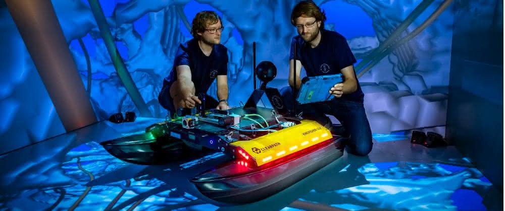 """Zwei Freiberger Informatiker an dem neu entwickelten Schwimmroboter """"Elisabeth"""" in der CAVE."""