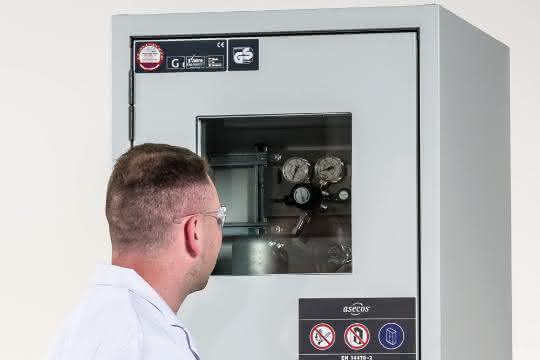 Mann im Kittel blickt durch das Türfenster des Druckgasflaschenschranks