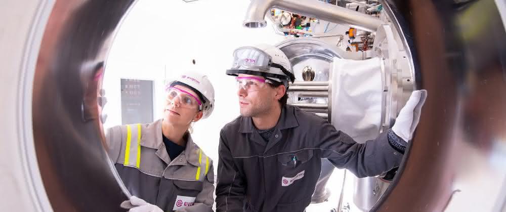 Zwei Personen blicken in Teil einer Anlage.