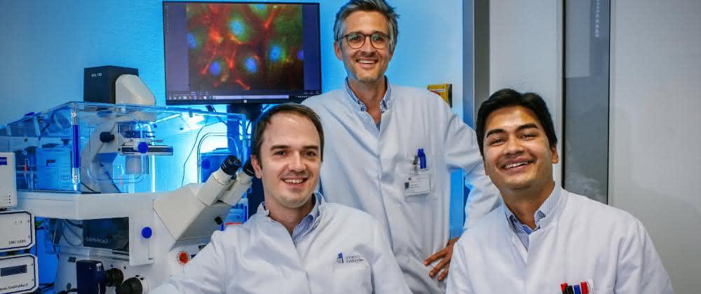 Andreas Zietzer, Felix Jansen und Rabiul Hosen neben einem Fluoreszenzmikroskop mit großem Bildschirm in einem Forschungslabor des Uniklinikums Bonn.