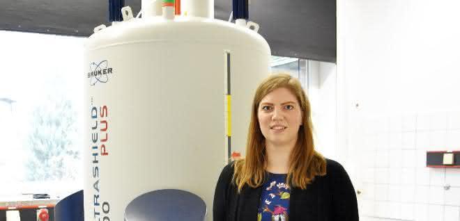 Anna McConnell im Labor neben einem Spektrometer.