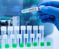 Probenröhrchen mit bedrucktem Etikett, im Hintergrund der Etikettierer AXON 2