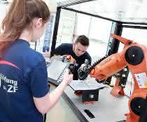 Roboterarm und programmierende Personen