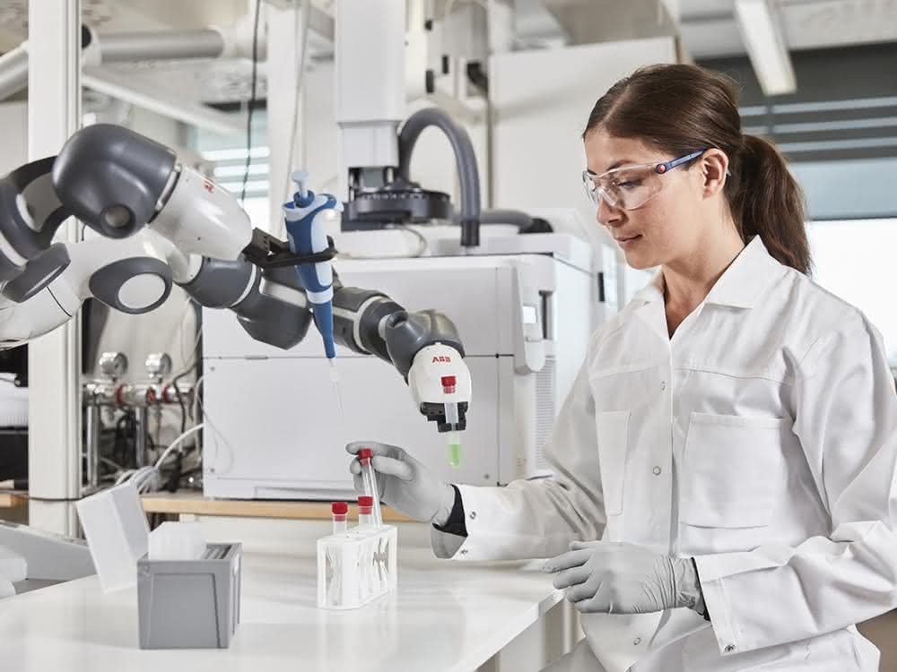 Roboterarm und Person in Laborkittel